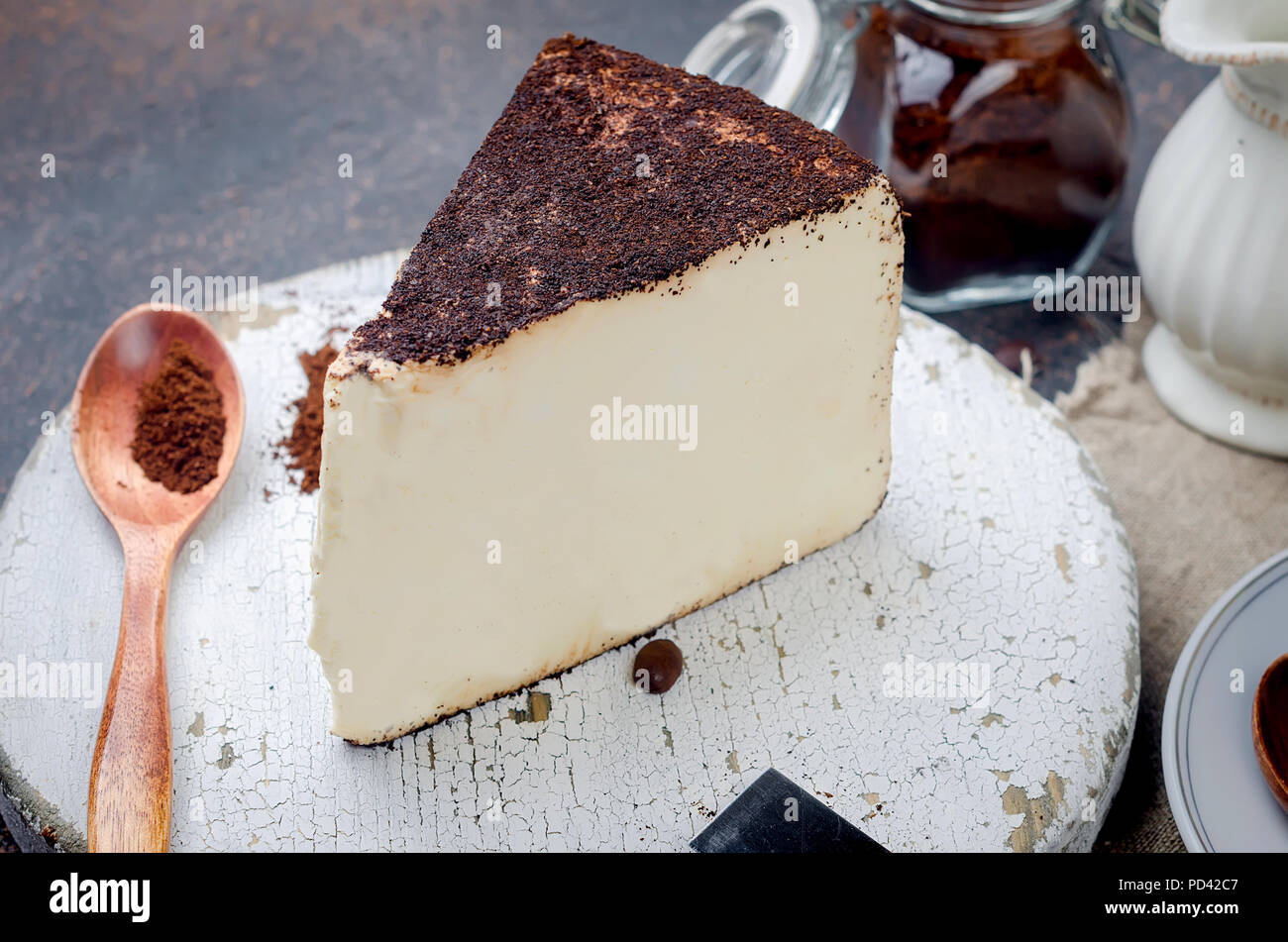 white cup of black coffee with a piece of soft cheese in coffee or cheesecake on dark background,  copy space - Stock Image