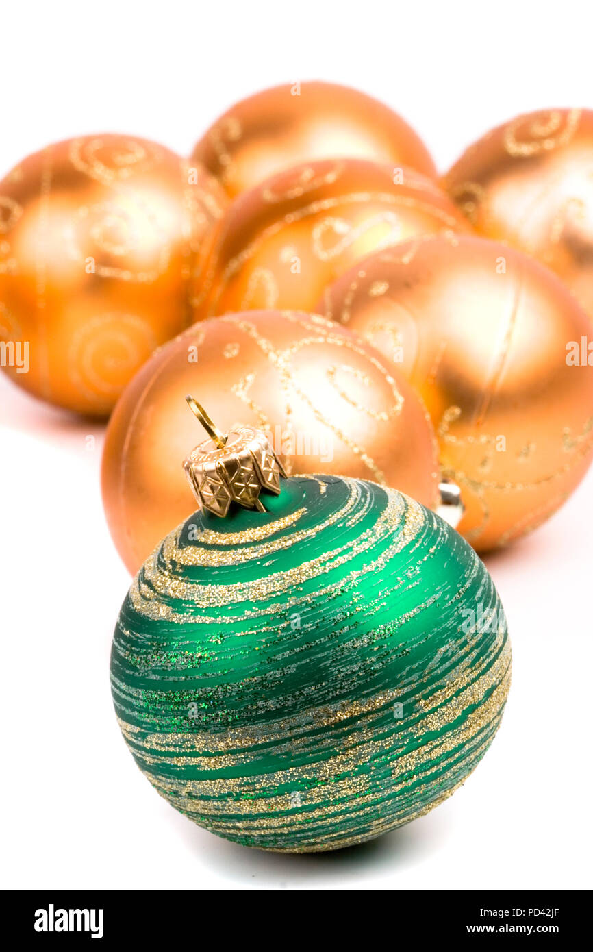 green and golden glass christmas balls closeup on white