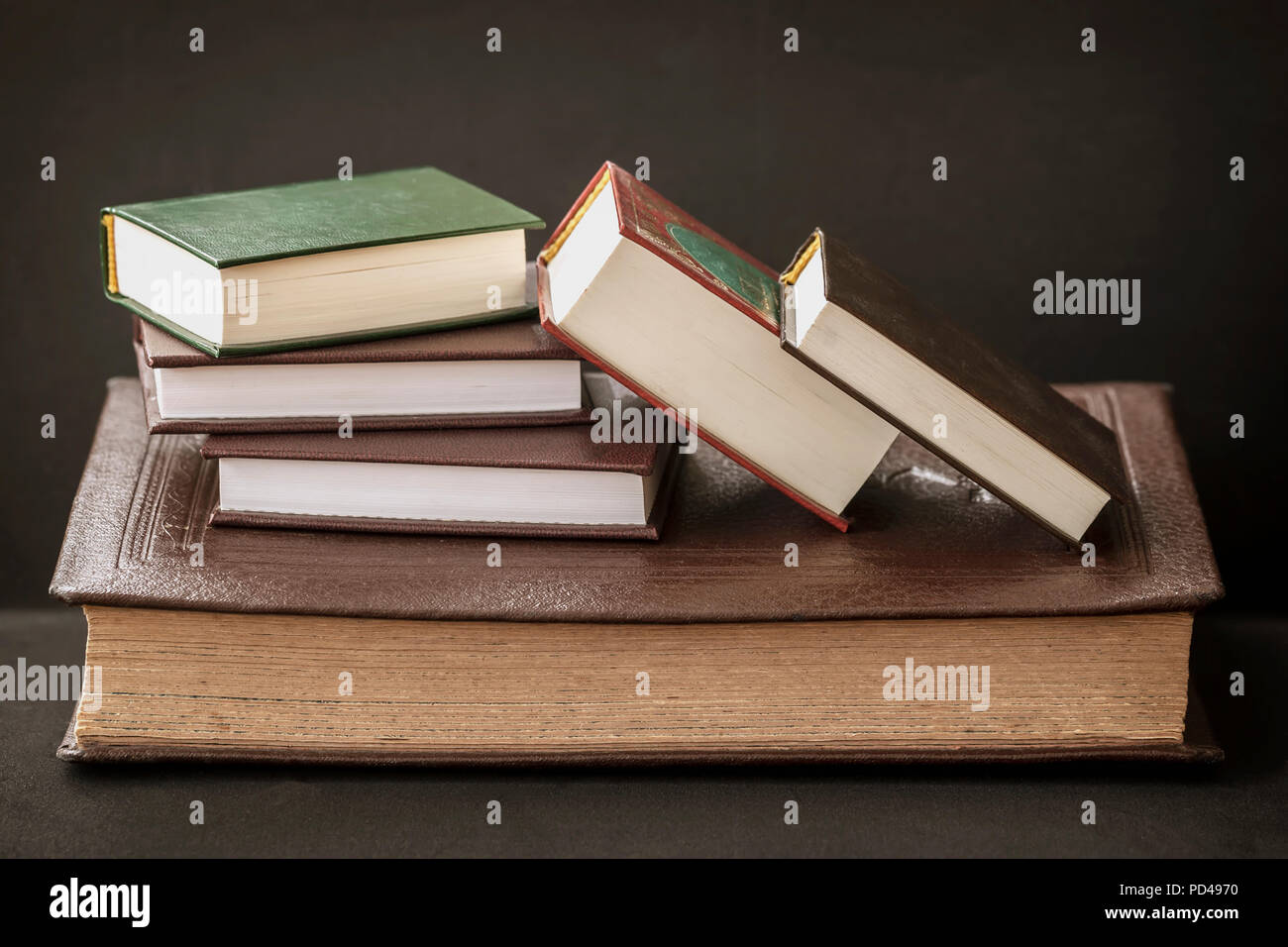 Several different sizes of books close up on a dark background - Stock Image