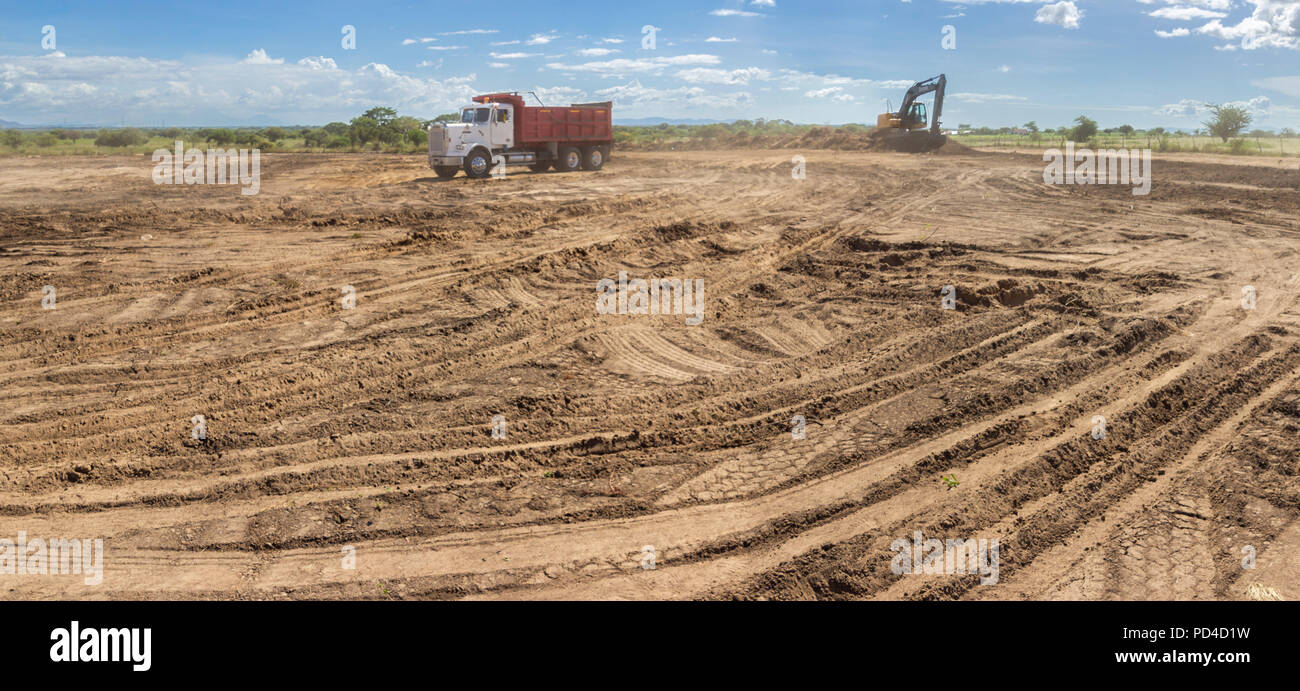 Trucks and heavy machinery clearing the land for the construction of a Solar Energy PV Plant at Choluteca, Honduras - Stock Image