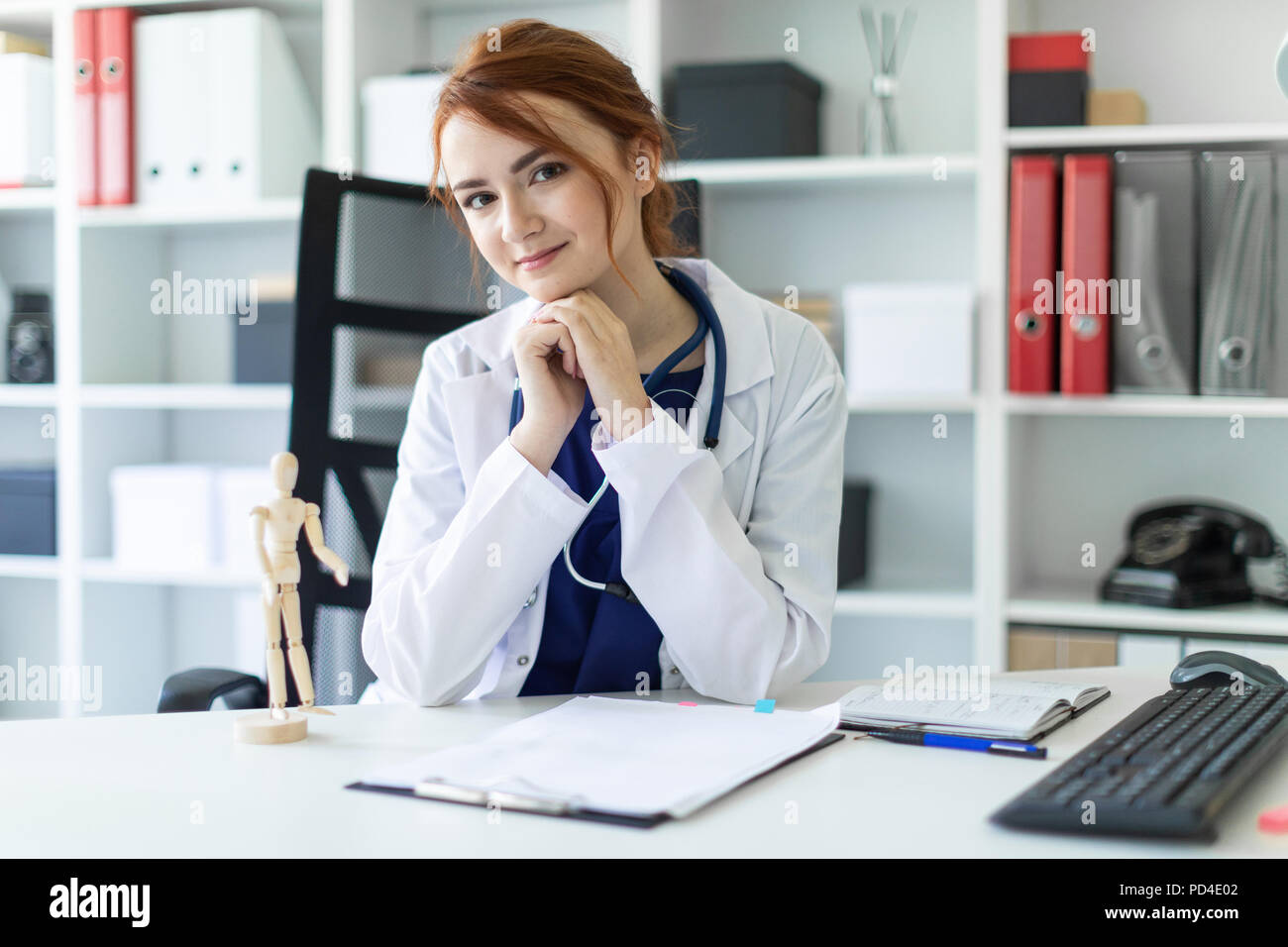 A beautiful young girl in a white robe is sitting at a table in the office. Stock Photo