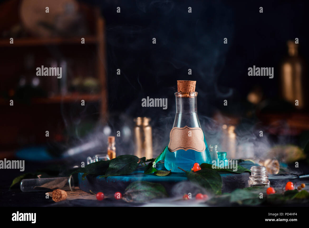 Blank label on a magic potion bottle. Modern witchcraft concept with potions, berries, herbs and occult equipment. Magical still life with copy space on a dark background. - Stock Image