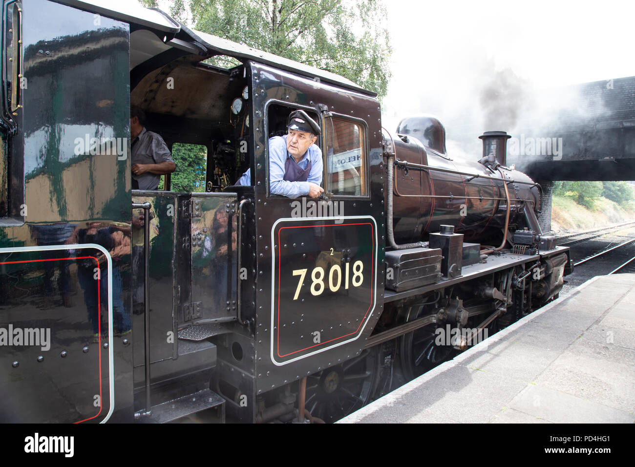 Engine driver on the footplate of No.78018 British Railways Standard Class 2 steam locomotive and looking out of the cab Stock Photo
