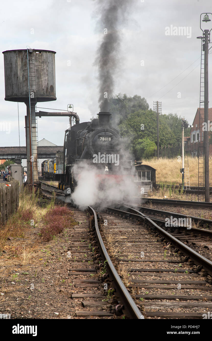British Railways Steam locomotive 4MT number 78018 taking on water and belching steam and black smoke on the sidings at Loughborough Heritage Railway Stock Photo