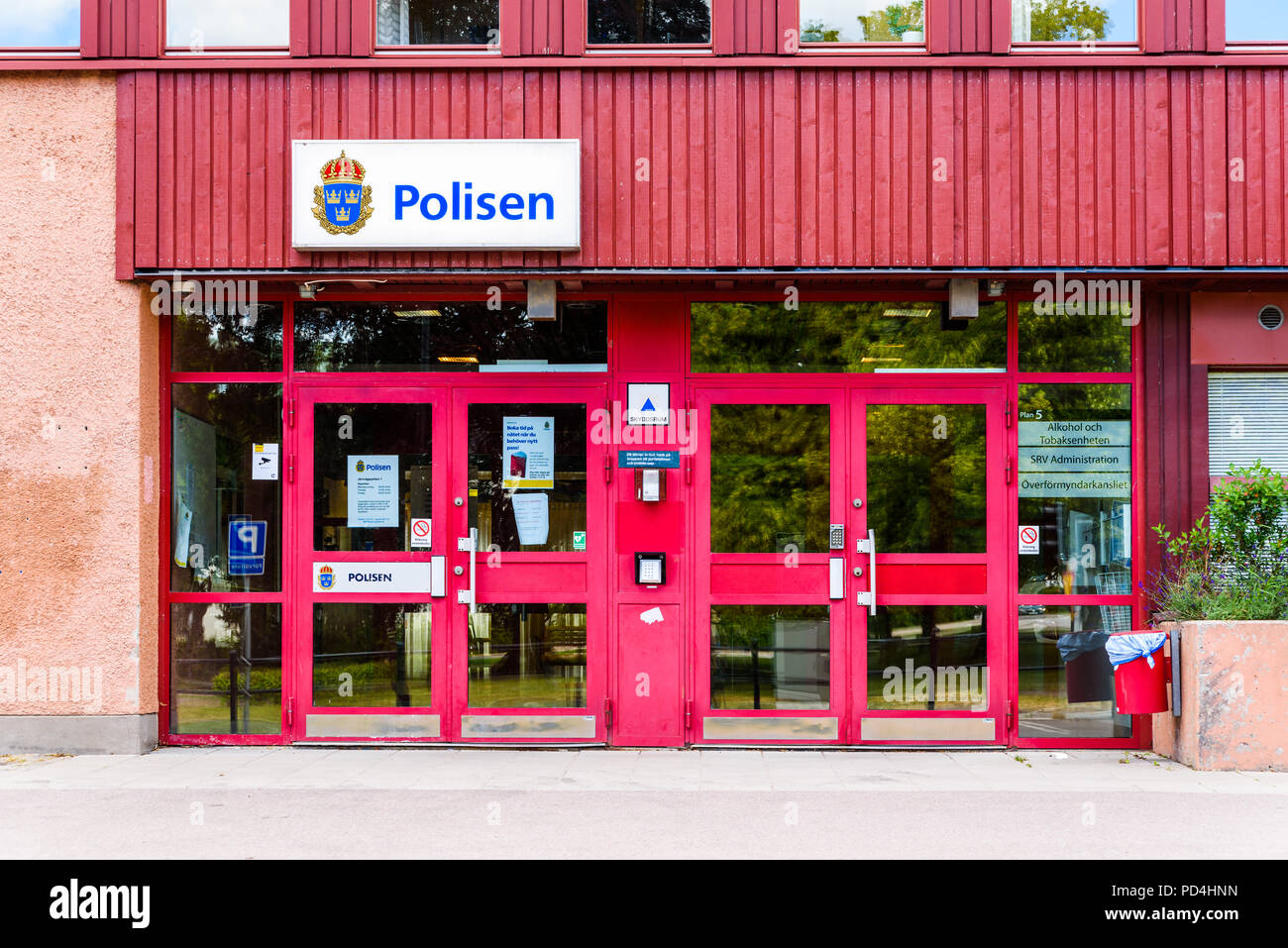 Motala, Sweden - June 30, 2018: The city police station on an ordinary day. No people visible. White sign on red facade. - Stock Image