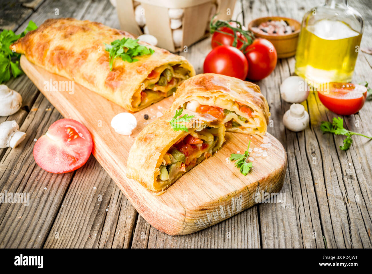 Vegetable savory strudel, homemade autumn baking, with tomatoes, bell pepper, mushrooms, wooden background copy space - Stock Image