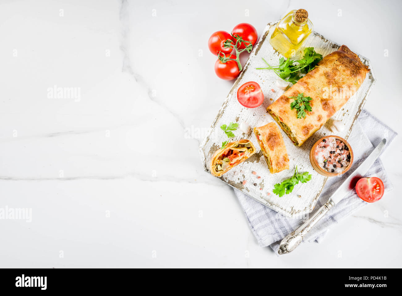Vegetable savory strudel, homemade autumn baking, with tomatoes, bell pepper, mushrooms, wooden background copy space Stock Photo