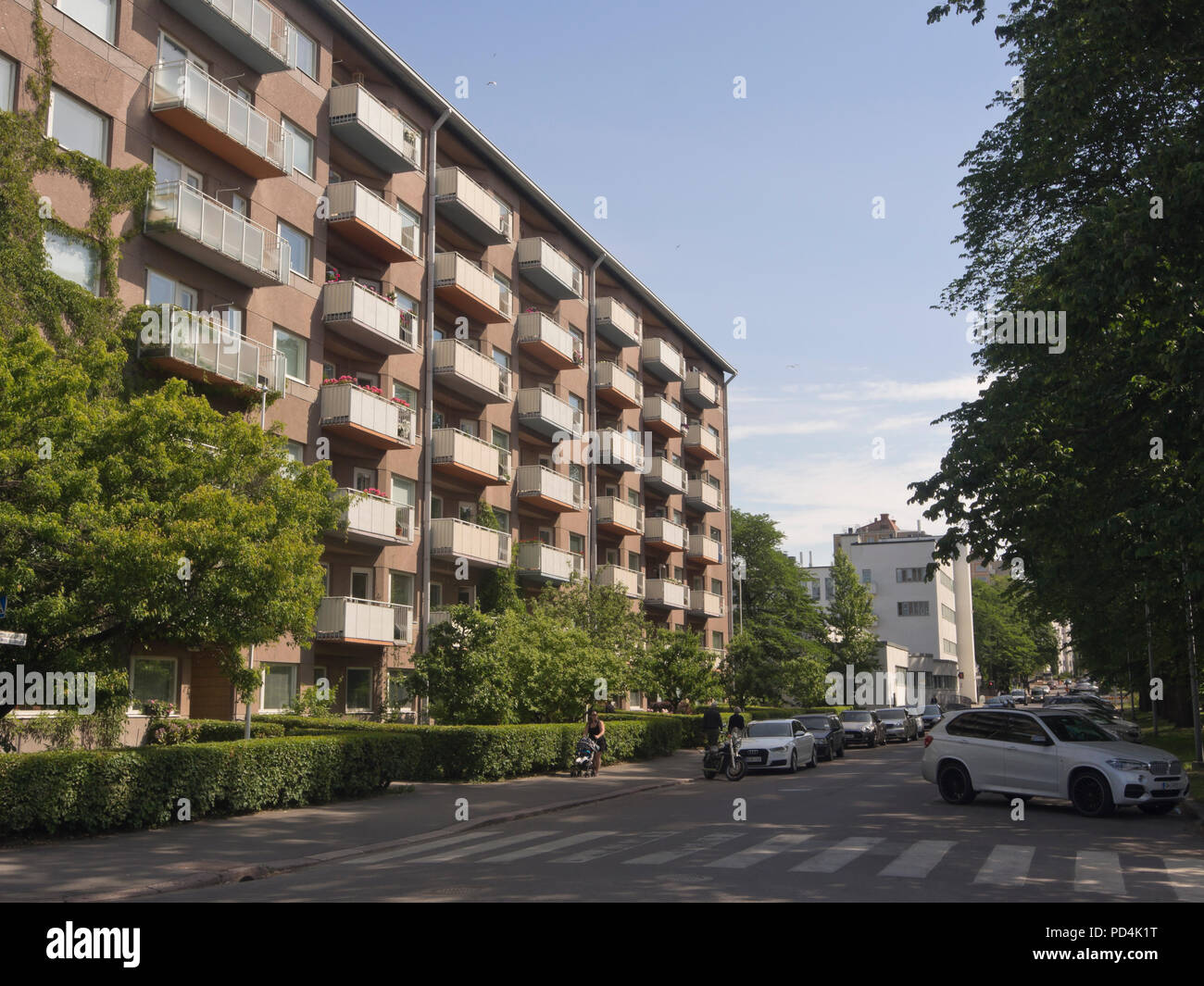 Residential area in the Tölö  district of Helsinki Finland apartment block with balconies, low hedge and parked vehicles on a quiet street - Stock Image