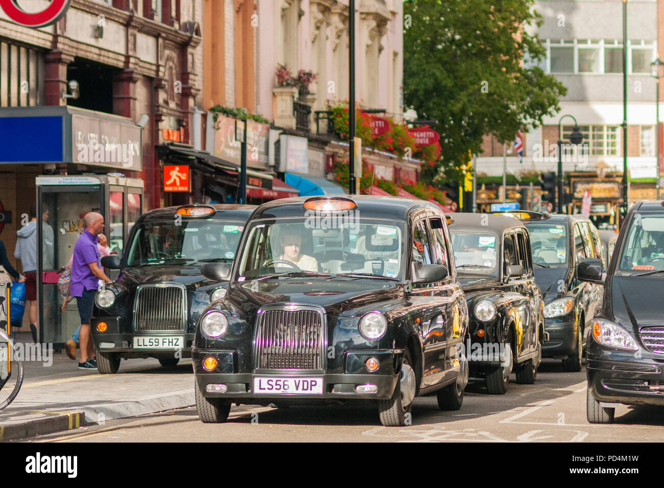 LONDON, UNITED KINGDOM - SEPTEMBER 12, 2012 Black cabs waiting for green signal at a traffic light near Leicester Square in London. - Stock Image