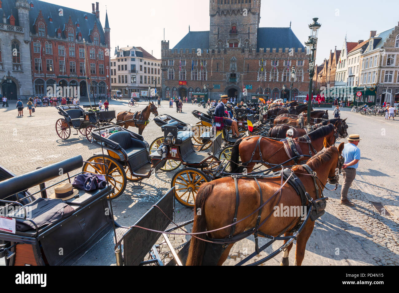 Horse and traps lined up in Markt Square near Bruges Belfry Bruges, Belgium. The horse and traps are used to take tourists on city tours - Stock Image