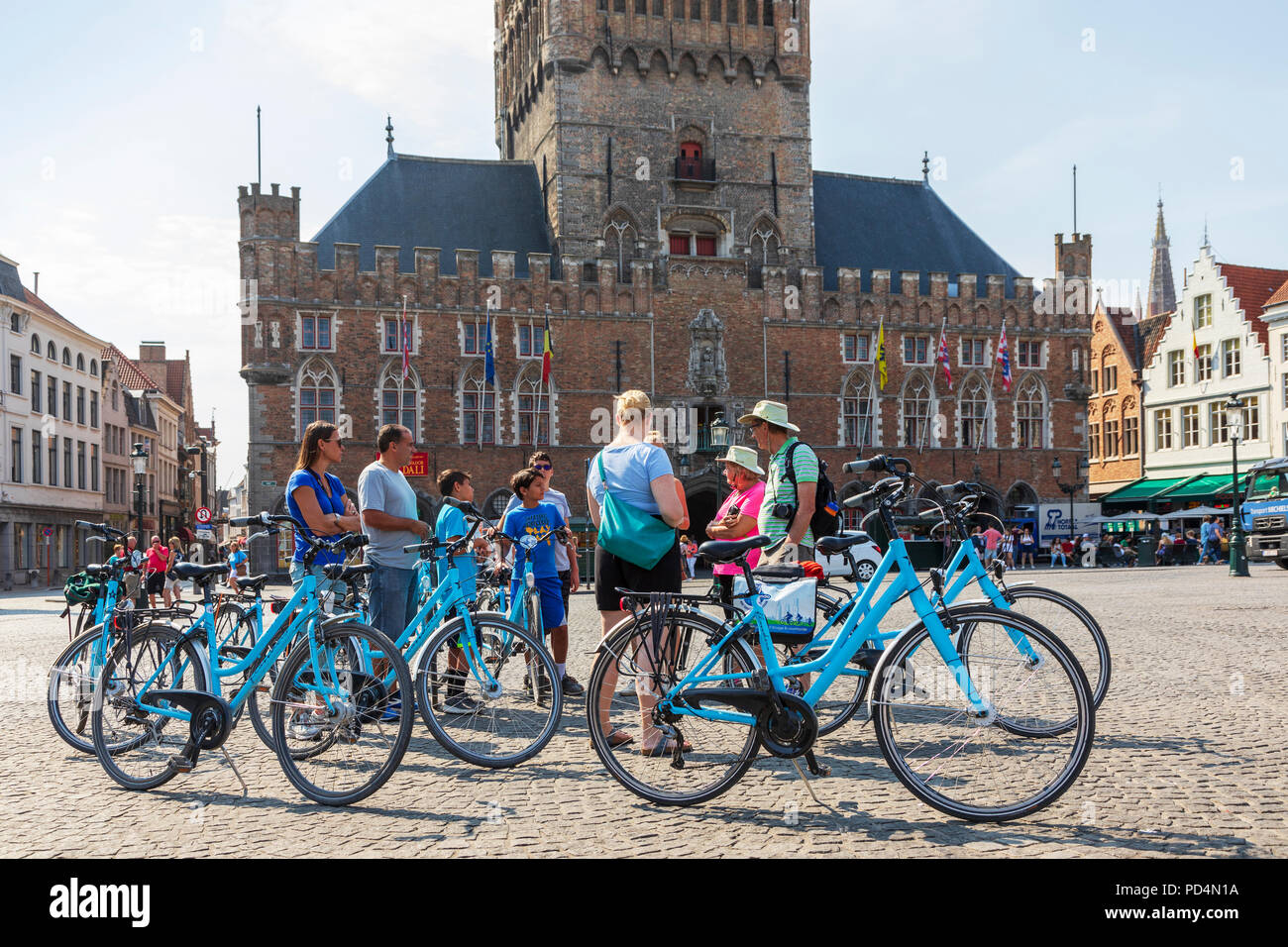 Tourists in Markt Square outside the Bruges Belfry on a cycle tour of Bruges, Belgium - Stock Image