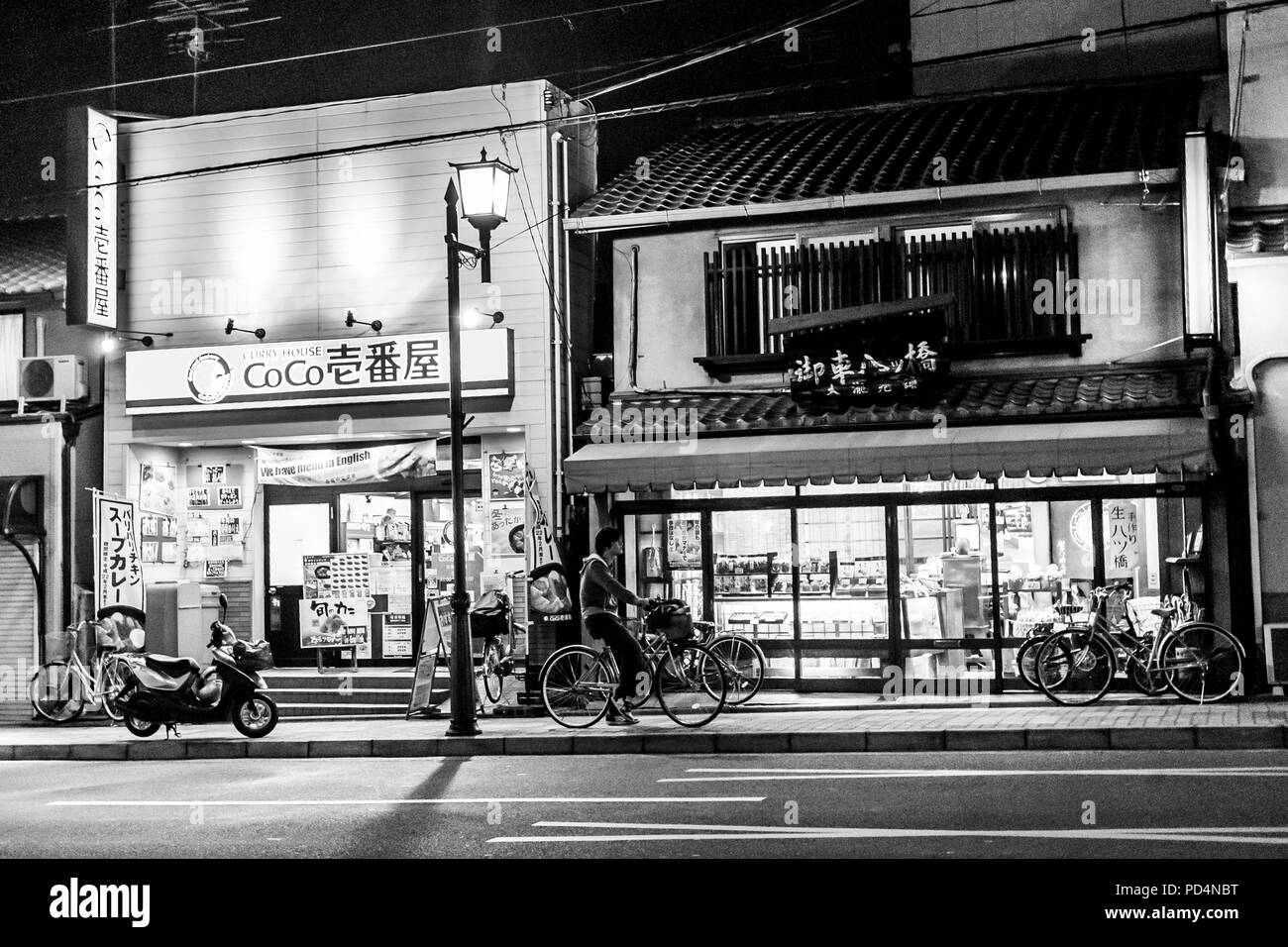 Kyoto, Japan.  A man on a bicycle near the store on Gion street at night - Stock Image