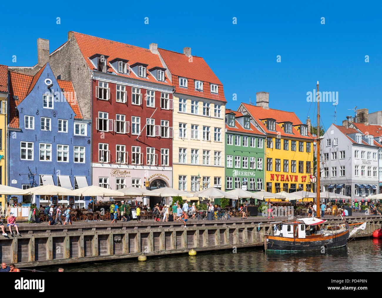 Historic buildings along Nyhavn canal, Copenhagen, Denmark. The oldest house is no 9 on the far left (blue building), Copenhagen, Denmark - Stock Image