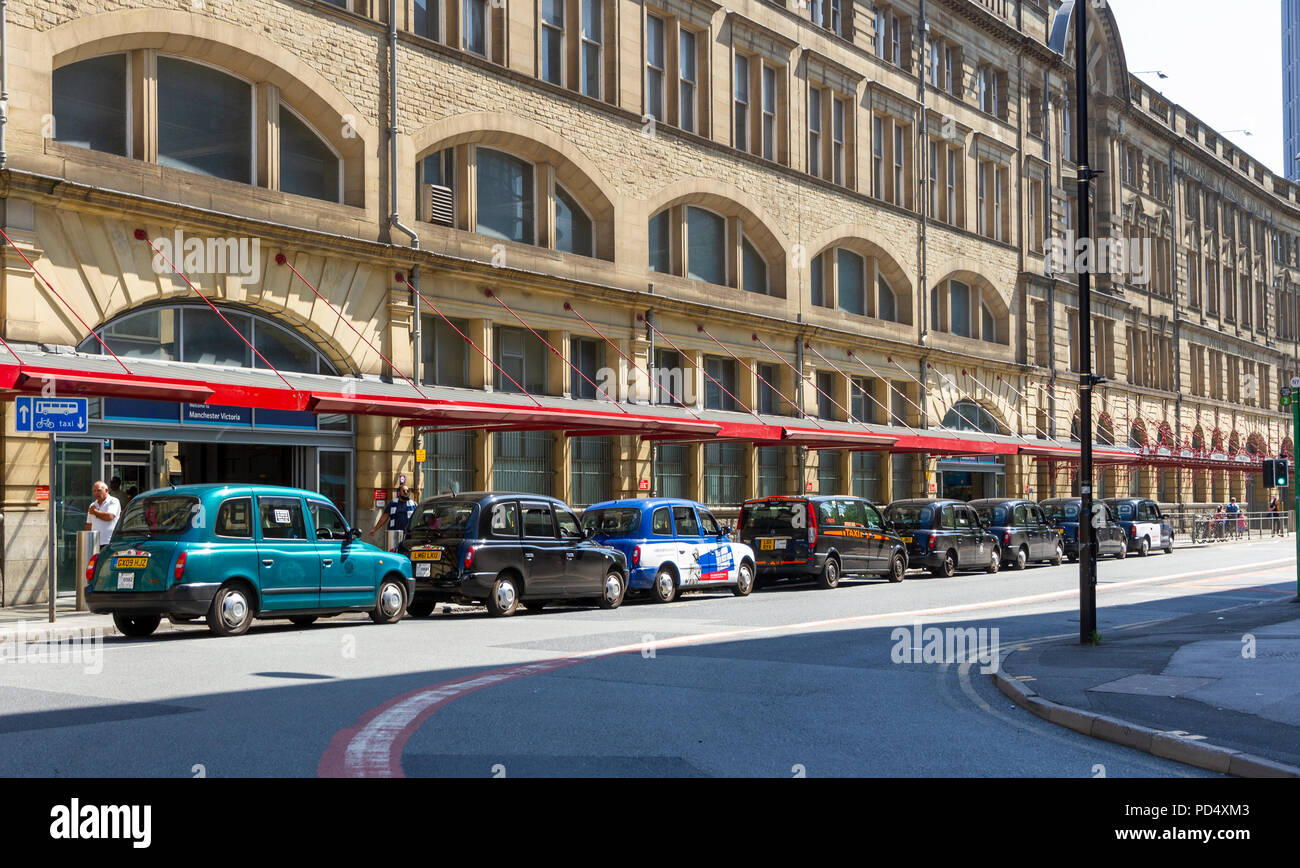 Taxi cabs lined up outside Victoria Train Station Manchester - Stock Image