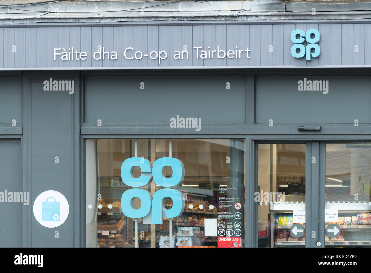 Scots gaelic sign on coop store in Tarbert - Failte dha co-op an Tairbeirt - welcome to the co-op Tarbert, Argyll and Bute, Scotland, UK - Stock Image