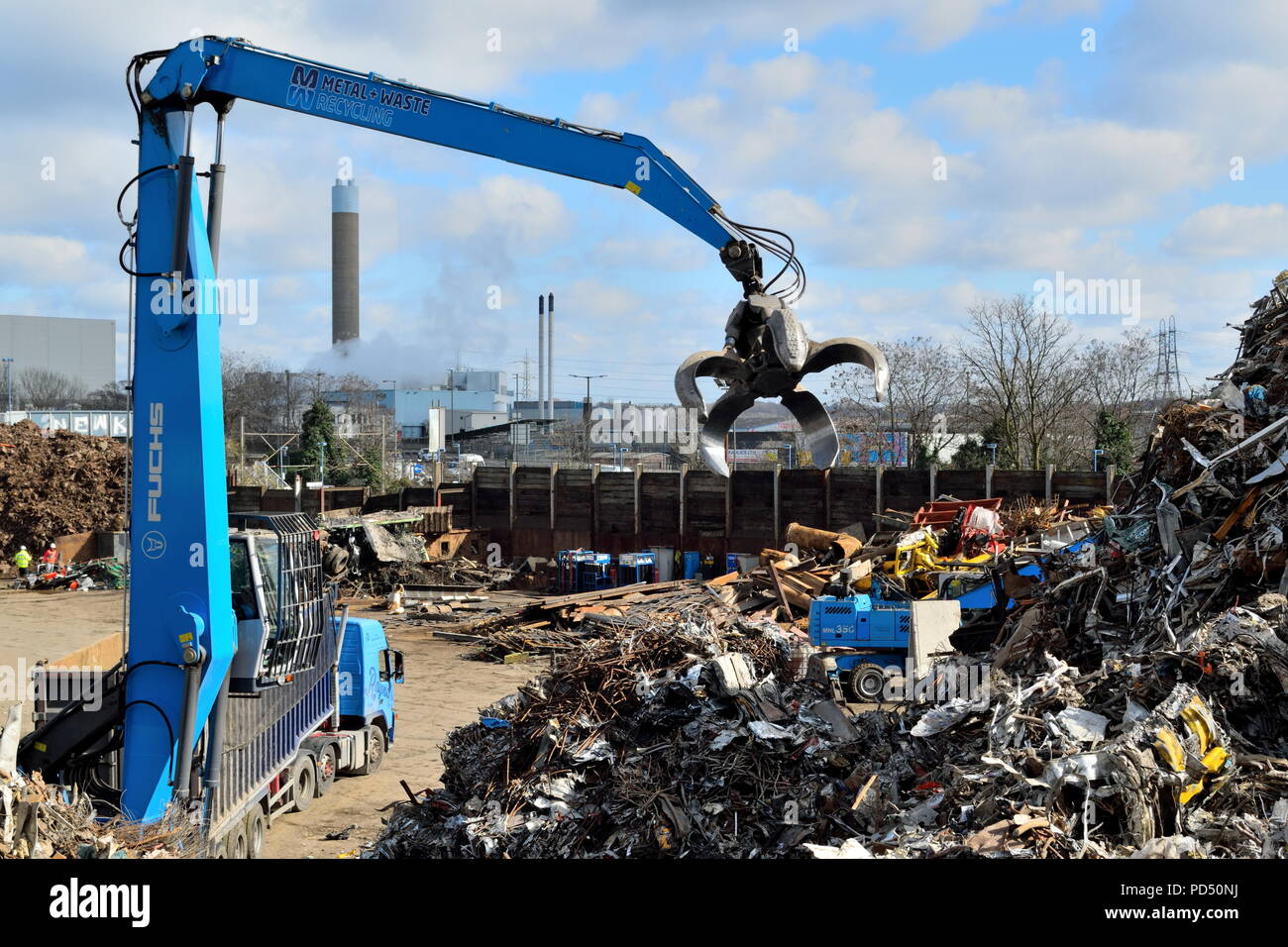 Excavating machine with large grapple claw on the scrap metal recycling site in Edmonton industrial estate, London. - Stock Image