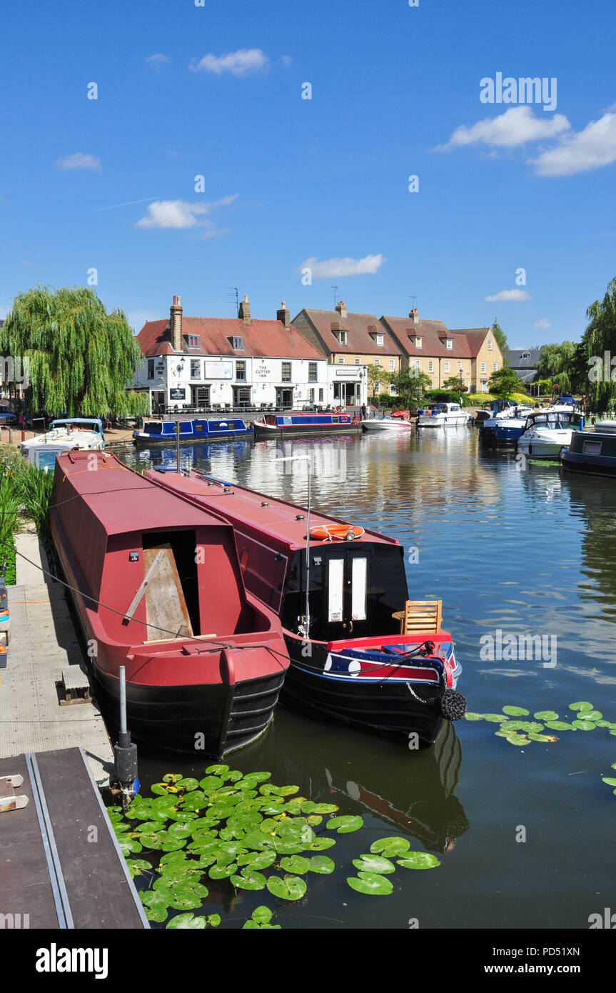 Narrow boats on the Great Ouse River with the Cutter Inn to the rear, Ely, Cambridgeshire, England, UK - Stock Image