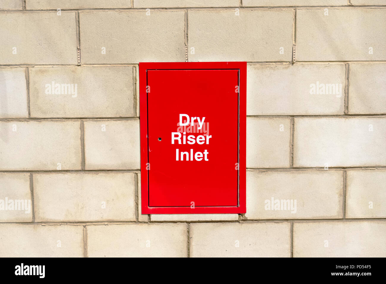 Dry riser inlet box red on brick wall for emergency fire services water connection for hose brigade engine at shopping mall retail park Stock Photo