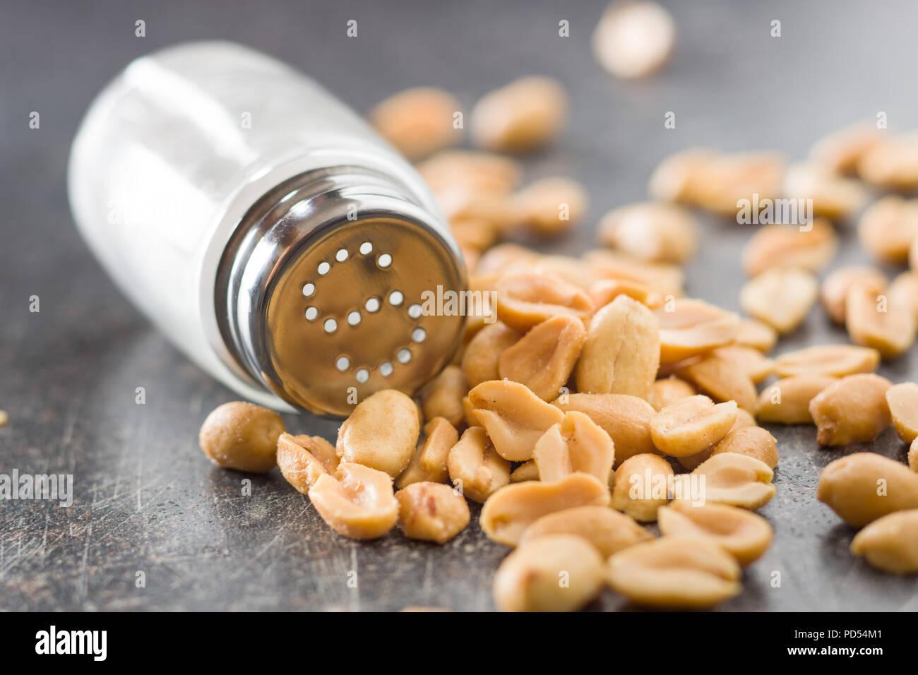 Salted roasted peanuts and salt cellar. - Stock Image