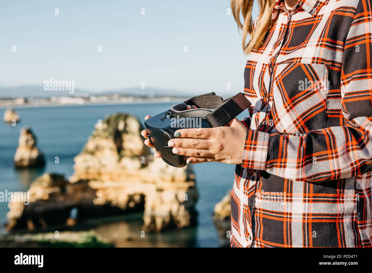 The girl is holding virtual reality glasses and is going to put them on. Conceptual photography of virtual travel or tourism. Modern technology in everyday life. - Stock Image