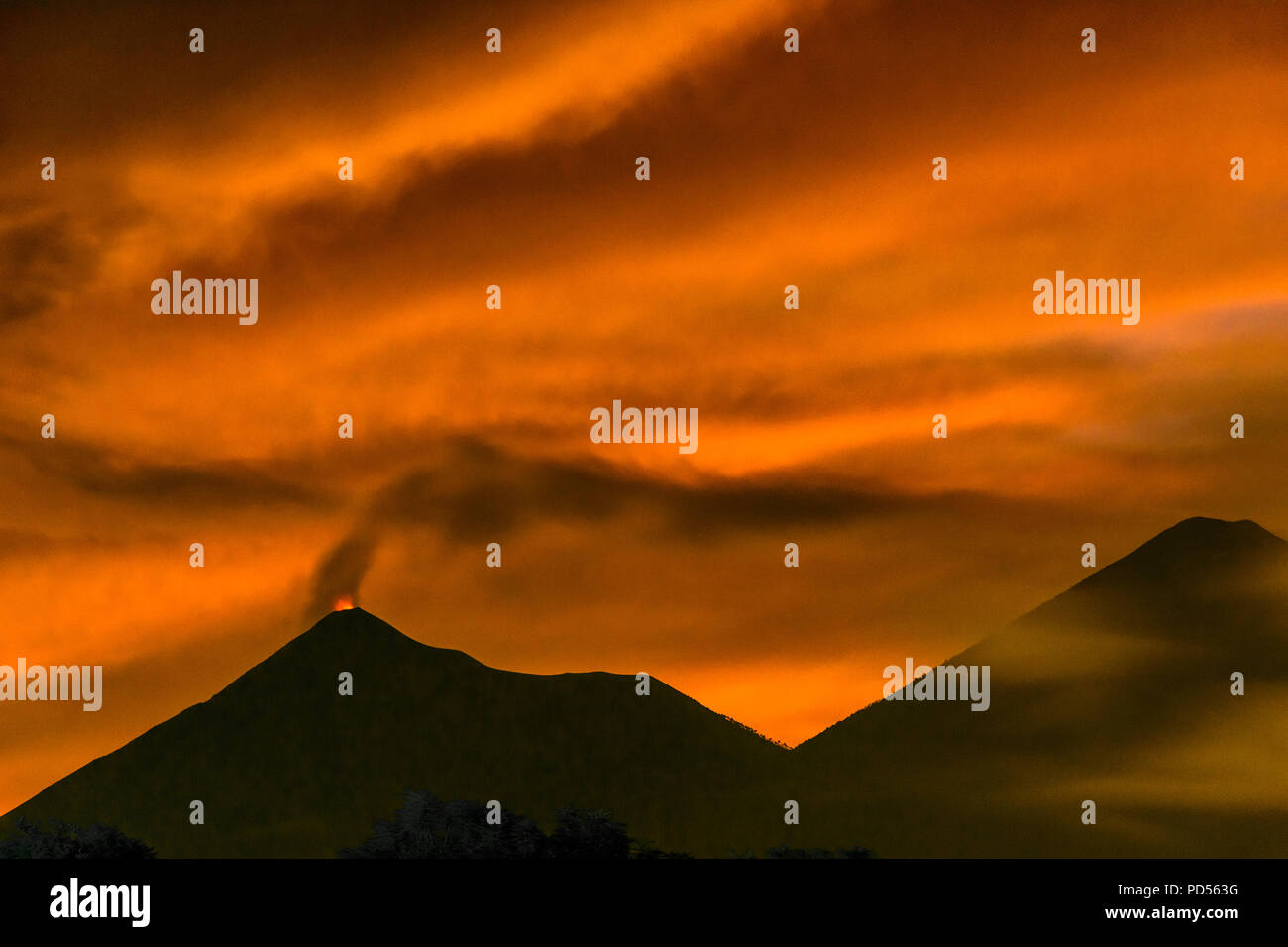 Fiery lava spurts from Fuego volcano in the Guatemalan highlands against fiery sunset hues as smoke ash clouds mingle with blur of clouds. - Stock Image
