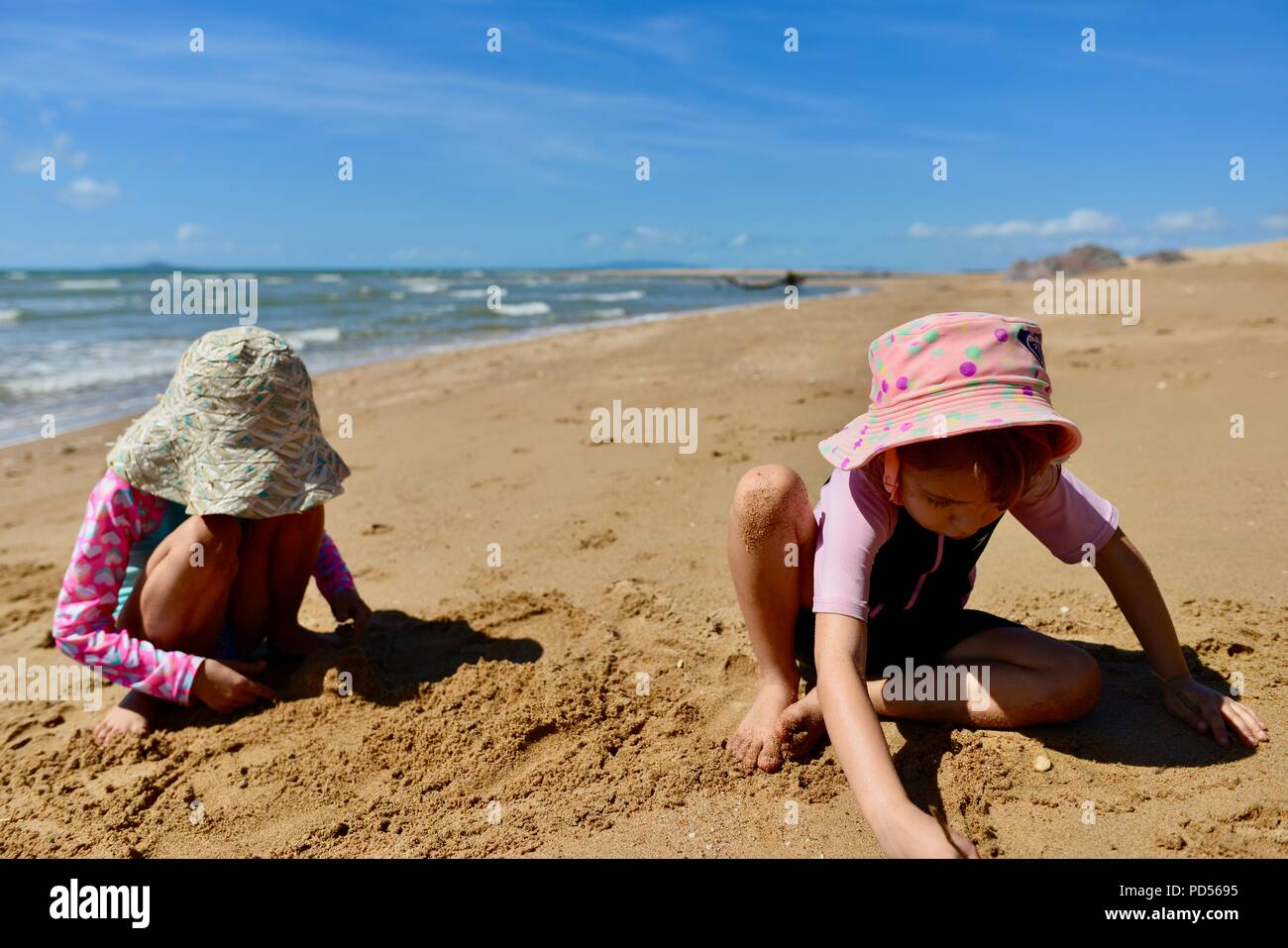 Two young girls playing in the sand on a deserted beach, Toomulla QLD, Australia - Stock Image