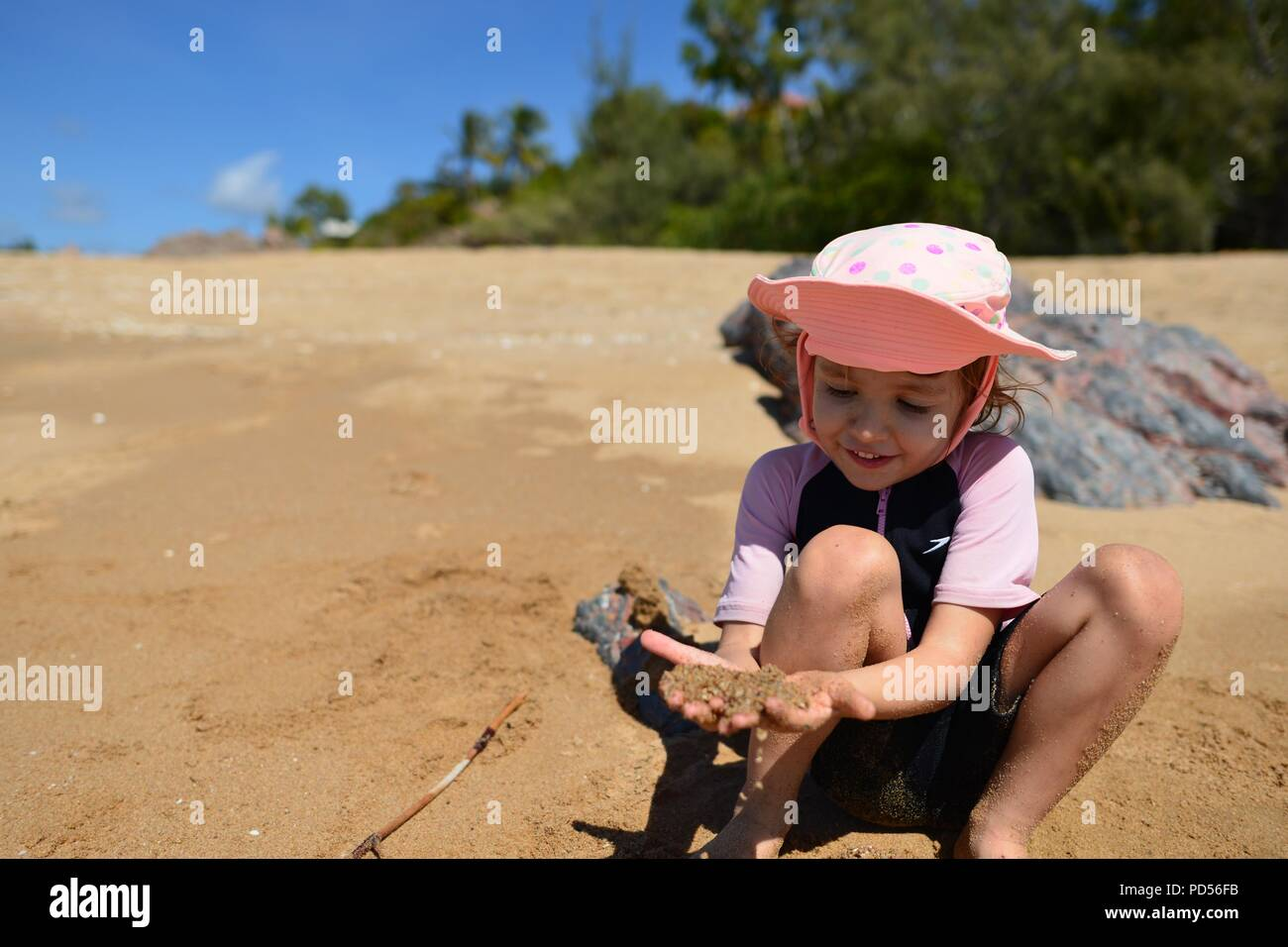 Young child playing on a beach looking at sand in her hand, Toomulla QLD, Australia - Stock Image