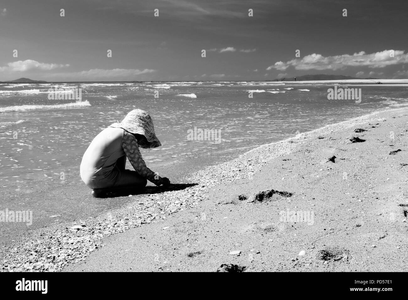 Young child playing on a deserted tropical beach, Toomulla QLD, Australia - Stock Image
