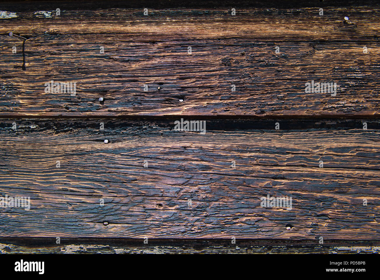 Weathered rustic wood plank background texture with yellow, black, and brown color tones - Stock Image