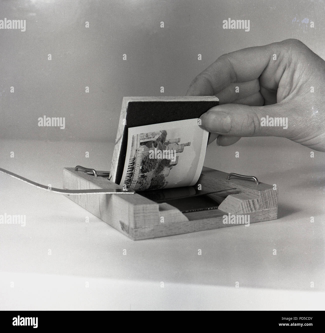 1950s, film photography, close-up showing a small contact print being produced from a film negative using a small wooden box. - Stock Image