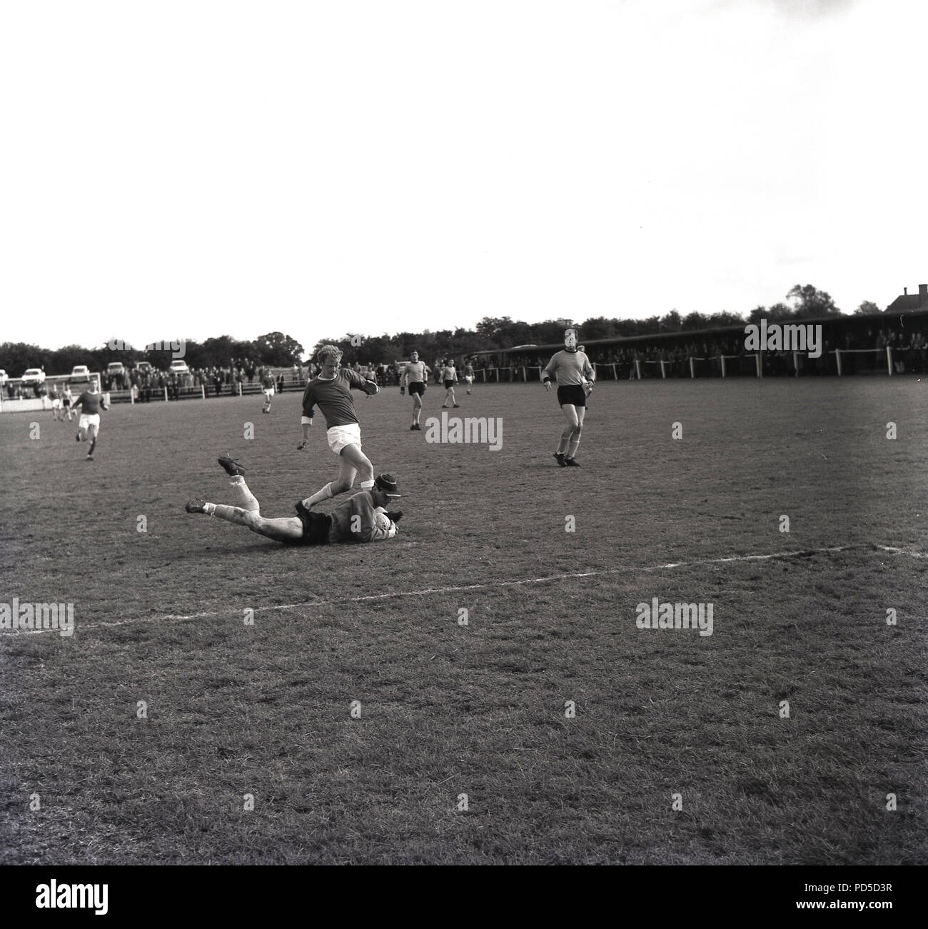 1960s semi-professional football match, goalkeeper wearing cap grans the ball at the feet of an oncoming striker, Aylesburry, Town FC, Aylesbury, Bucks, England, UK. - Stock Image