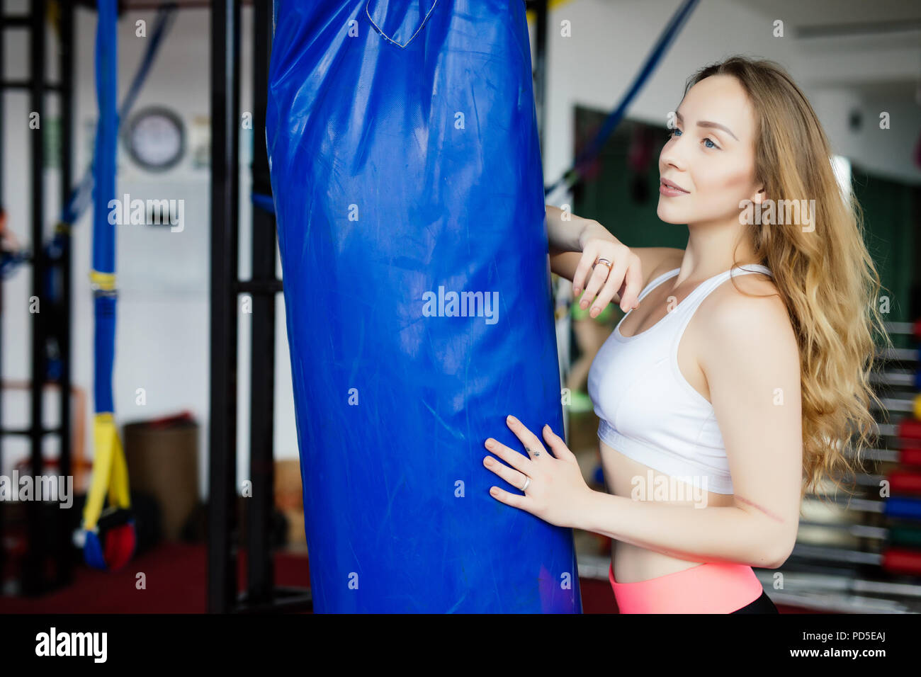 Crossfit fitness woman boxing with punching bag at gym - Stock Image