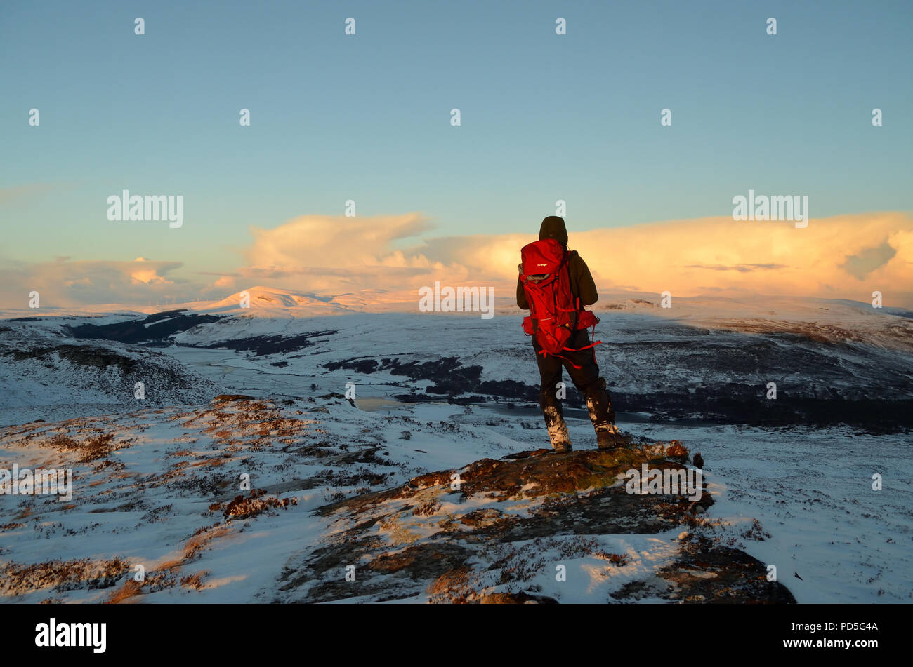 A hill walker standing on a ridge looking at a snow covered landscape in the Scottish Highlands, UK - Stock Image