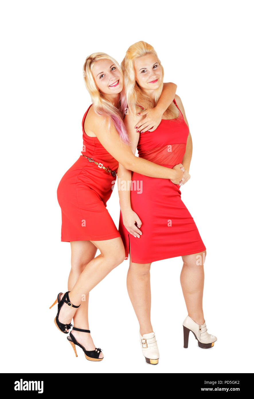 Couple smiling blonde girls in red dresses on high heels isolated on white background.  Lovely sisters - Stock Image