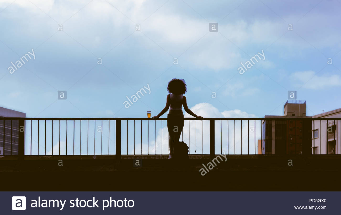 Full length portrait of a young woman standing in concrete bridge. Urban scene of girl in contemplation. cup of juice in railings. Copy space and sky. - Stock Image