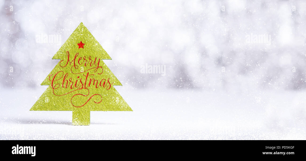 Close up Merry Christmas word on green Christmas tree with sparkling red star with snow fall on white floor at silver background bokeh light,Banner mo - Stock Image