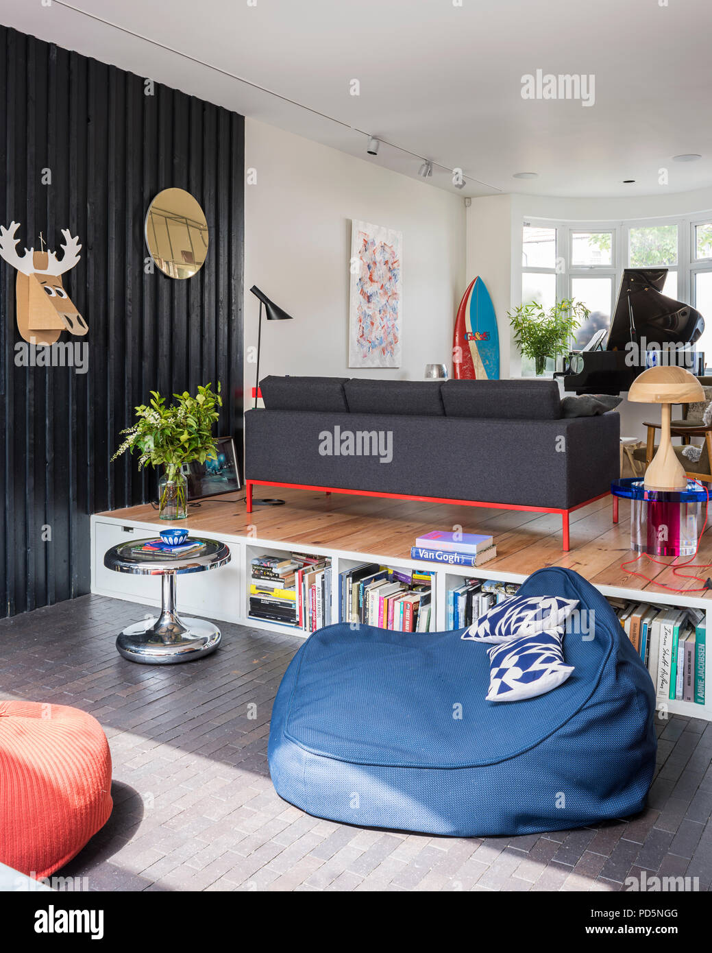 Open plan family home with timber clad walls and wood lamp designed by Andy Martin - Stock Image