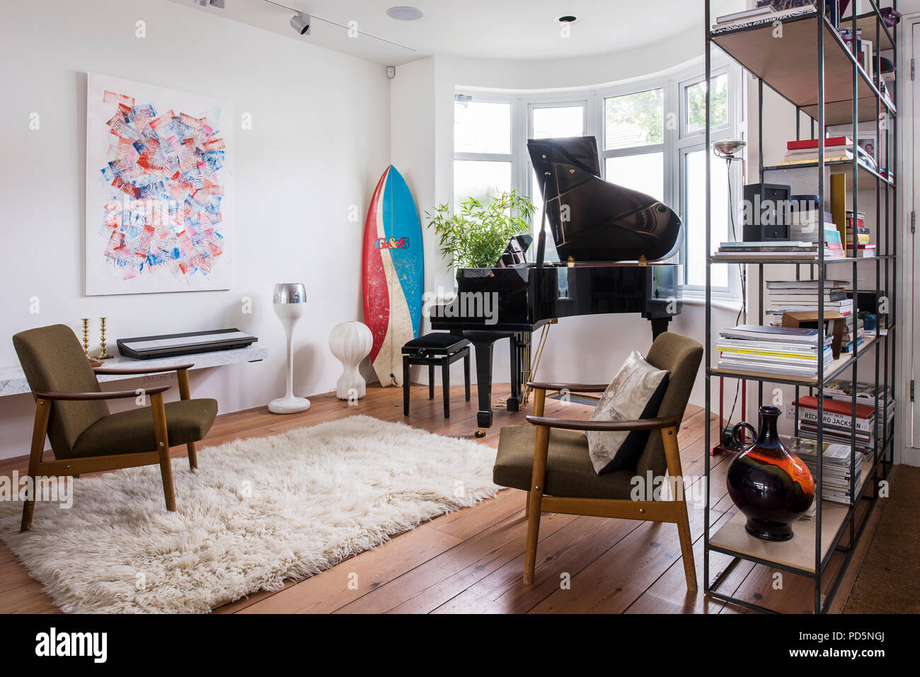 Open plan family home with surf board, grand piano and pair of retro armchairs - Stock Image