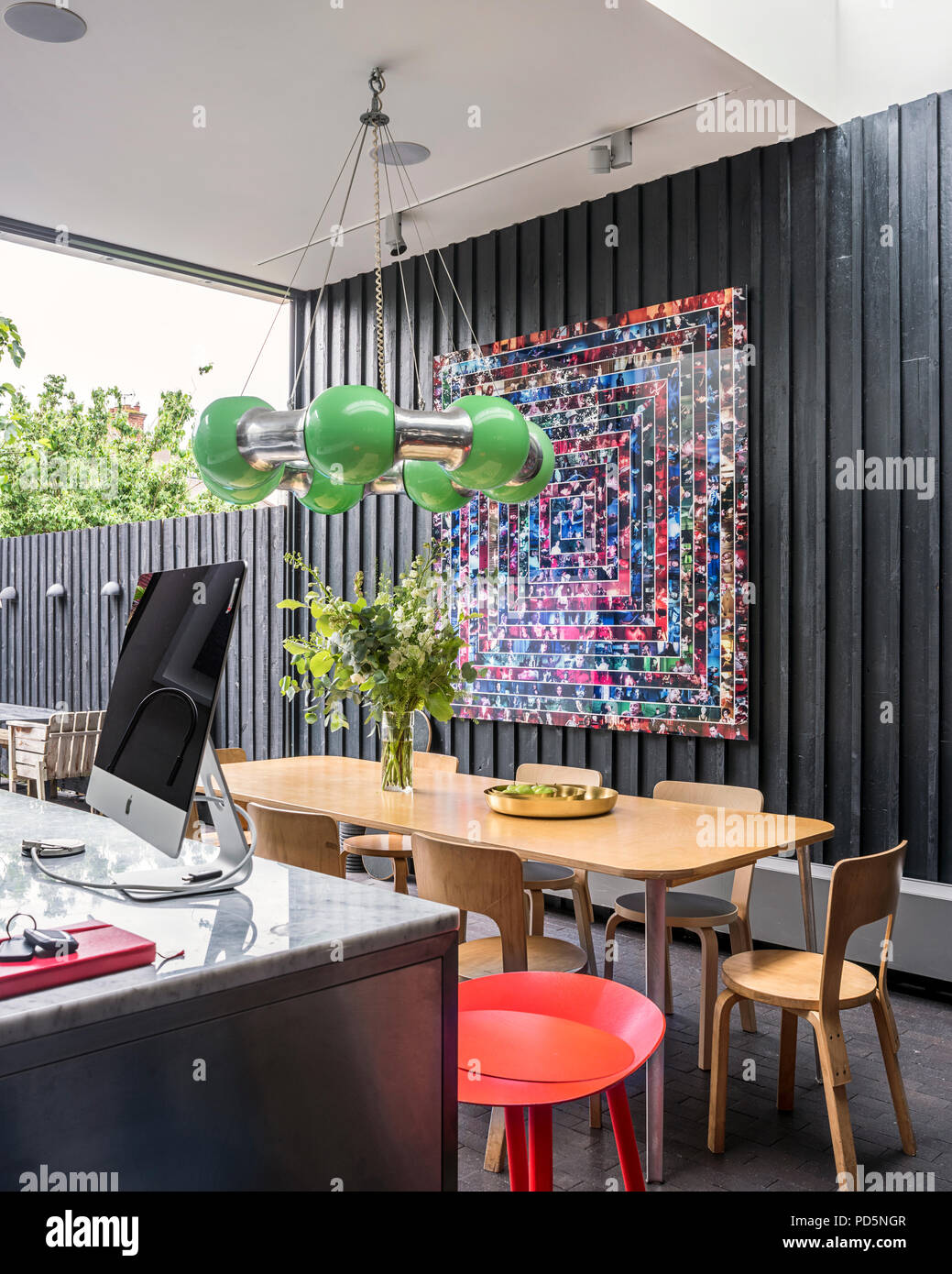 Open plan family home with timber clad walls and green lamp is designed by Andy Martin. - Stock Image