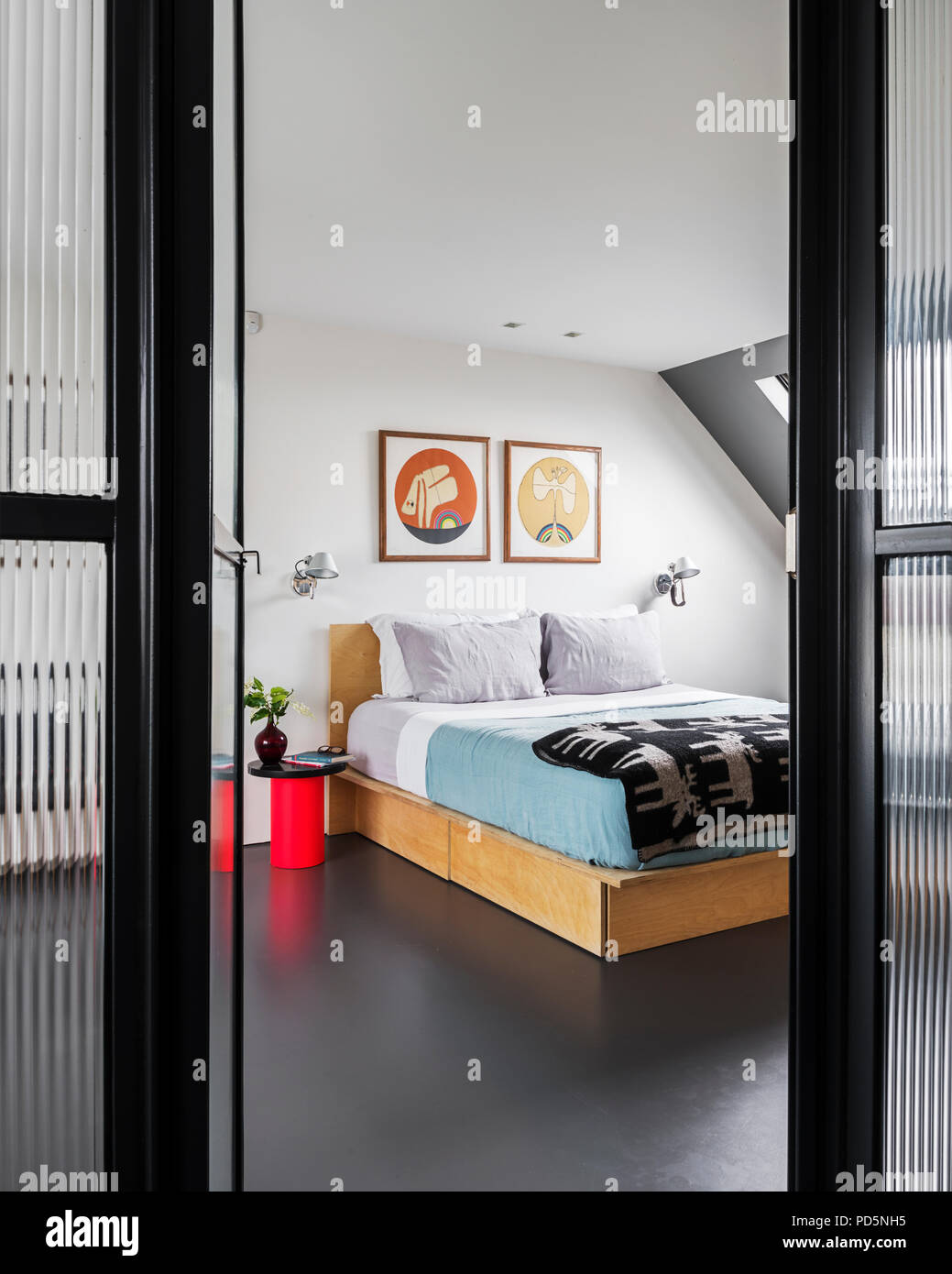 View through corrugated style glass wall into minimal style bedroom - Stock Image