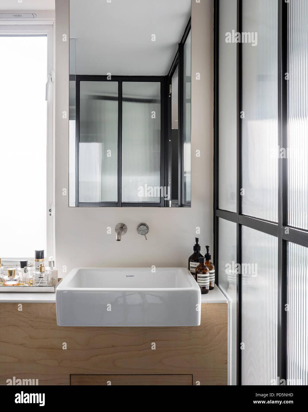 Elegant vanity area with corrugated glass panels and ceramic basin - Stock Image