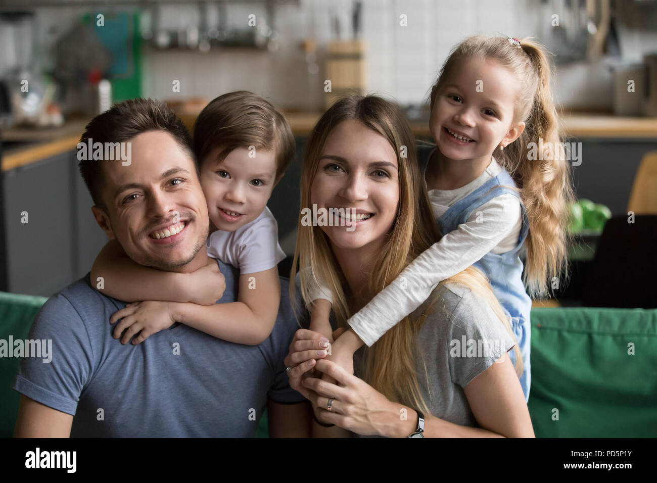 Happy parents piggybacking son and daughter sitting on sofa, por - Stock Image