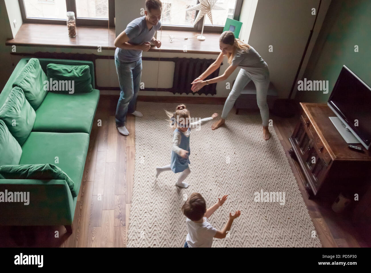 Happy family with children playing hide and seek game together - Stock Image