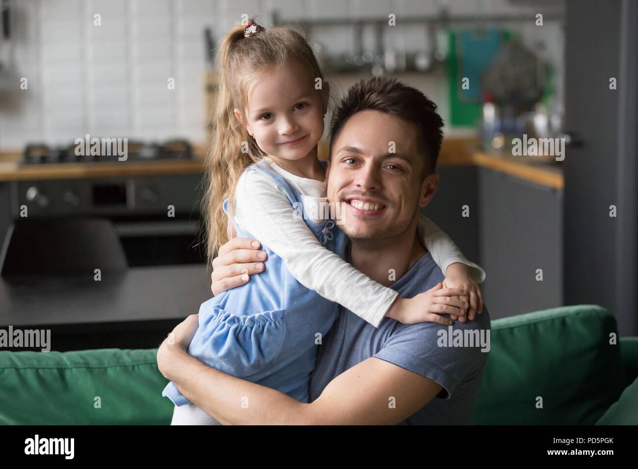Portrait of happy dad hugging kid daughter looking at camera  - Stock Image