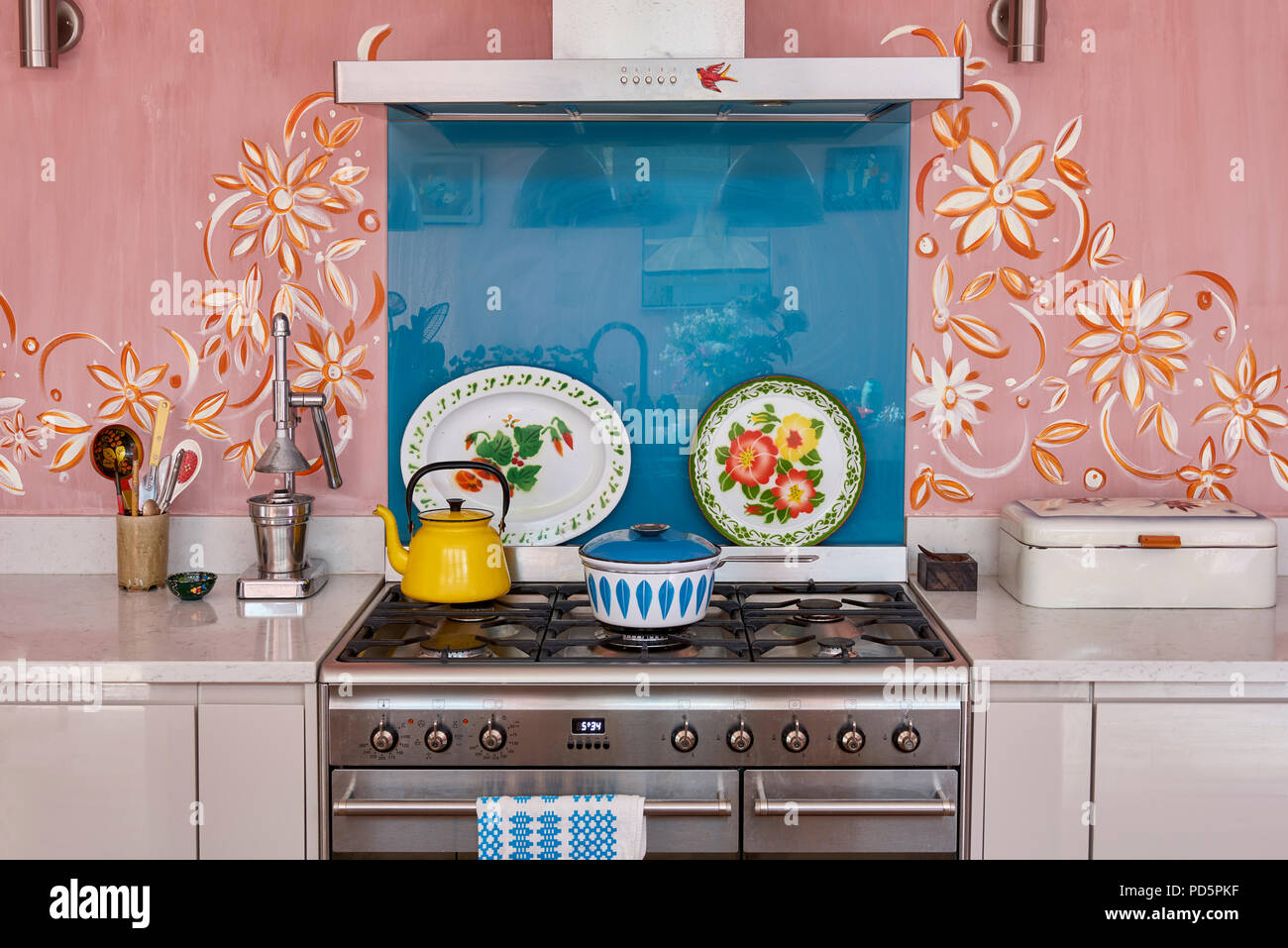Swedish folk art inspired mural painted by Jo Oakley frames the cooker. The kettle and decorative platter dishes are enamelware - Stock Image