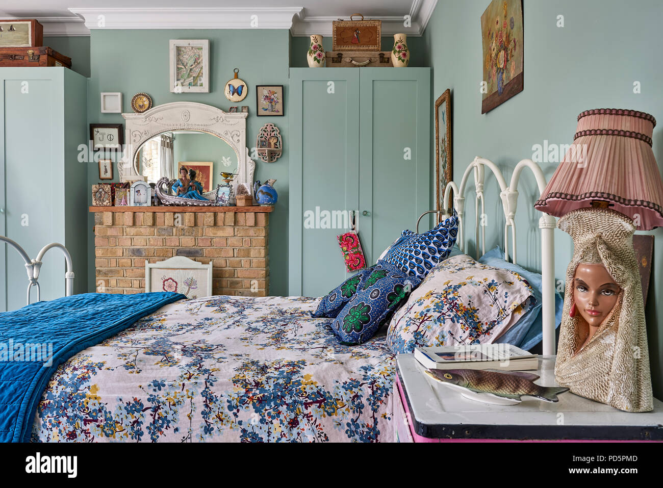 A pair of simple Shaker style cupboards in bedroom painted in Little Greene's Cupboard Green. The floral bedlinen is from sainsburys and the cushions  - Stock Image