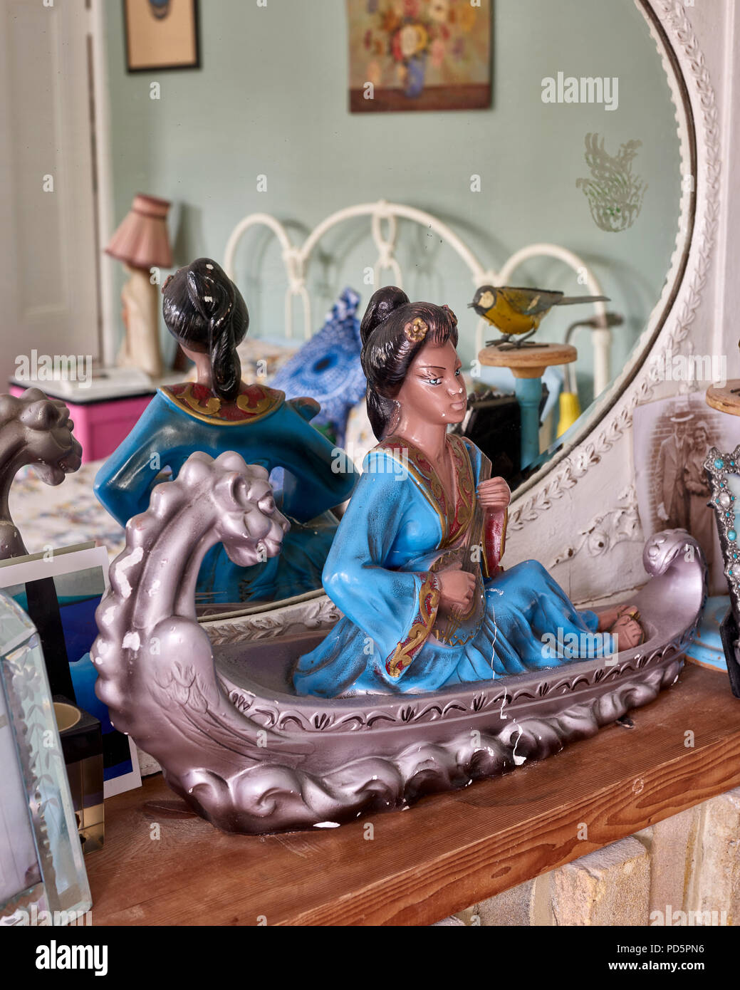 A kitsch chinese ornament of a girl in a dragon canoe - Stock Image