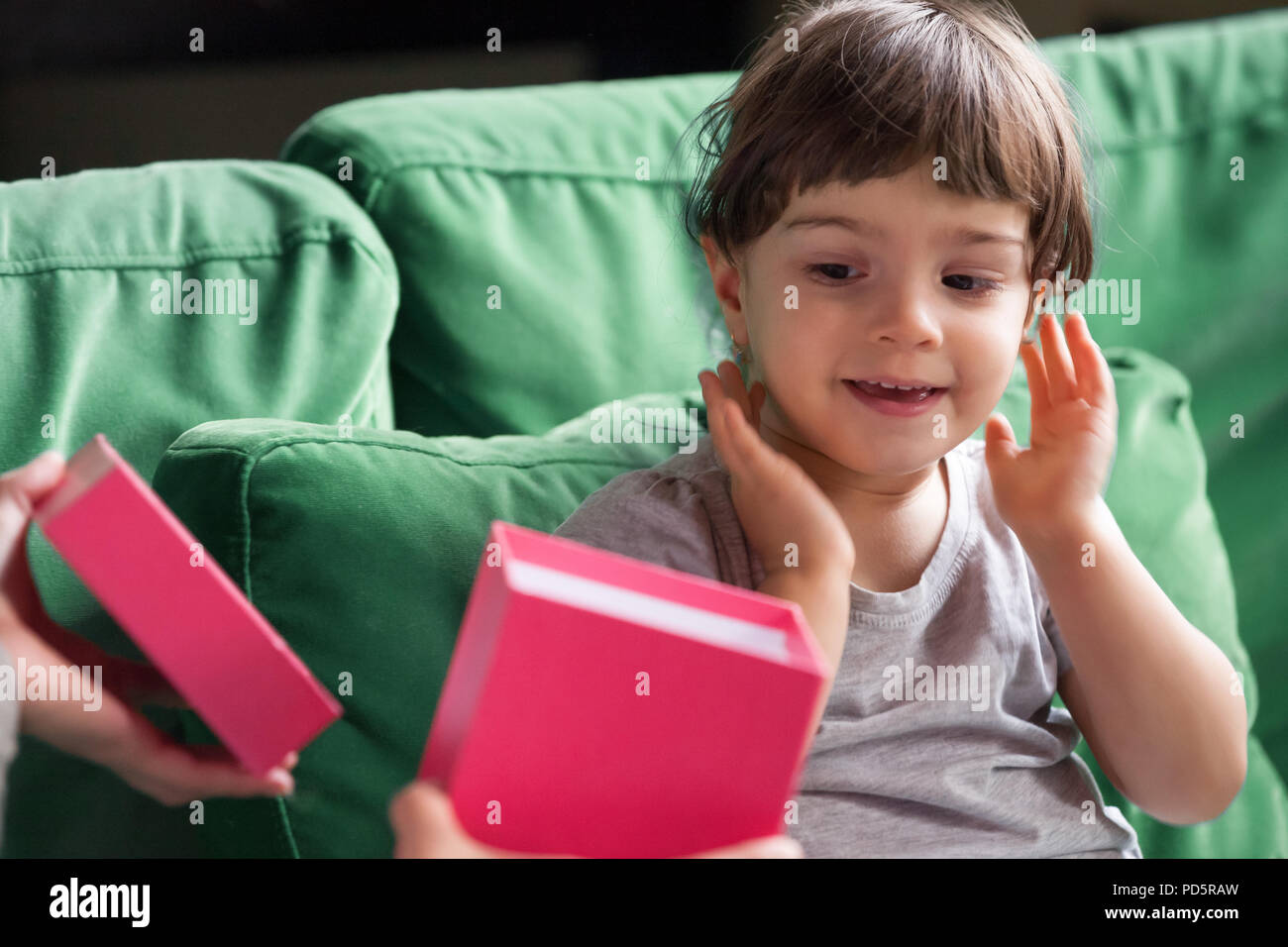 Curious shy kid girl looking inside gift box with present - Stock Image