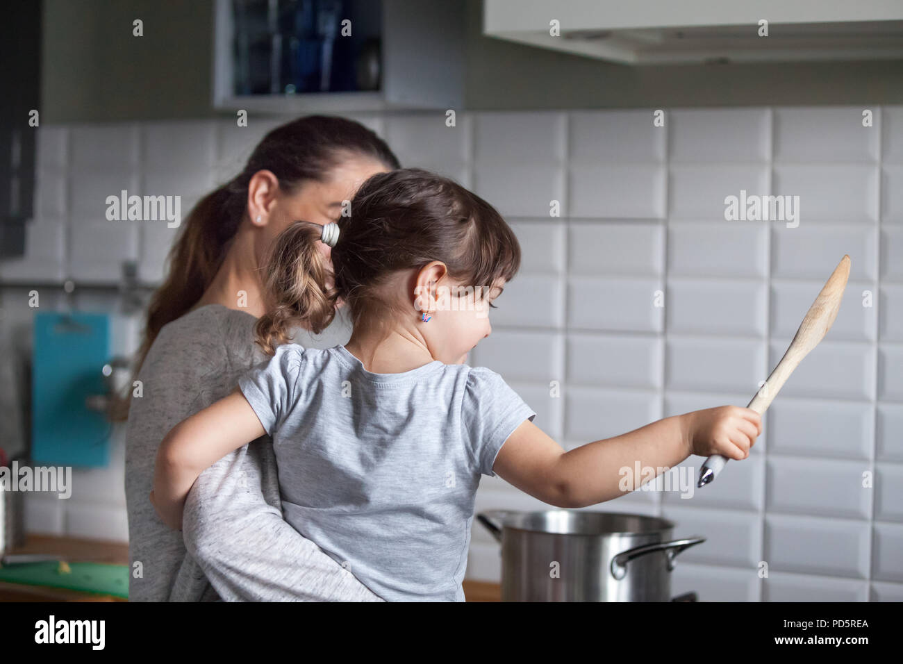Rear view at mother holding child daughter helping to cook - Stock Image