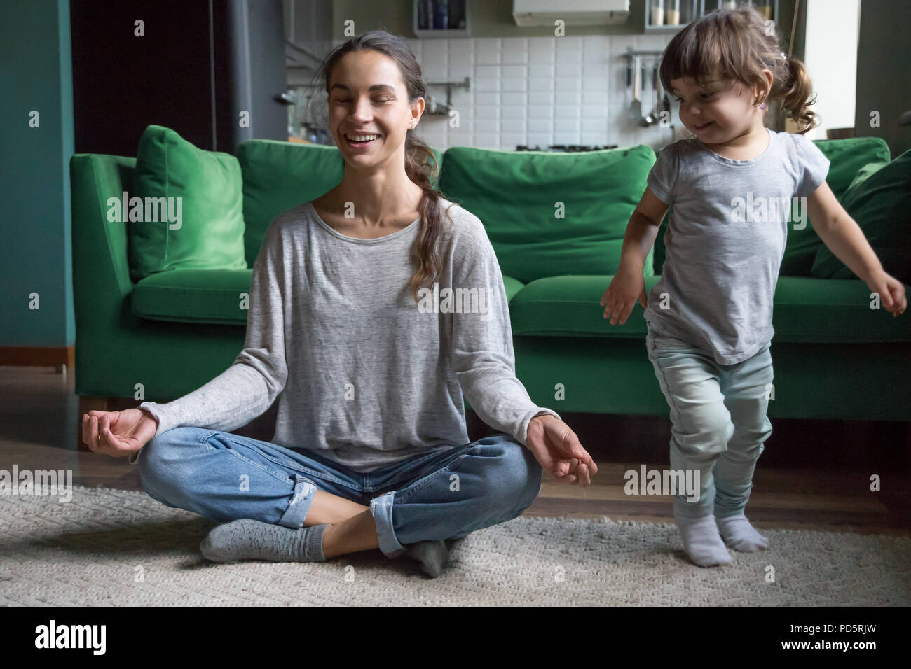 Happy mindful mother doing yoga with kid playing at home - Stock Image